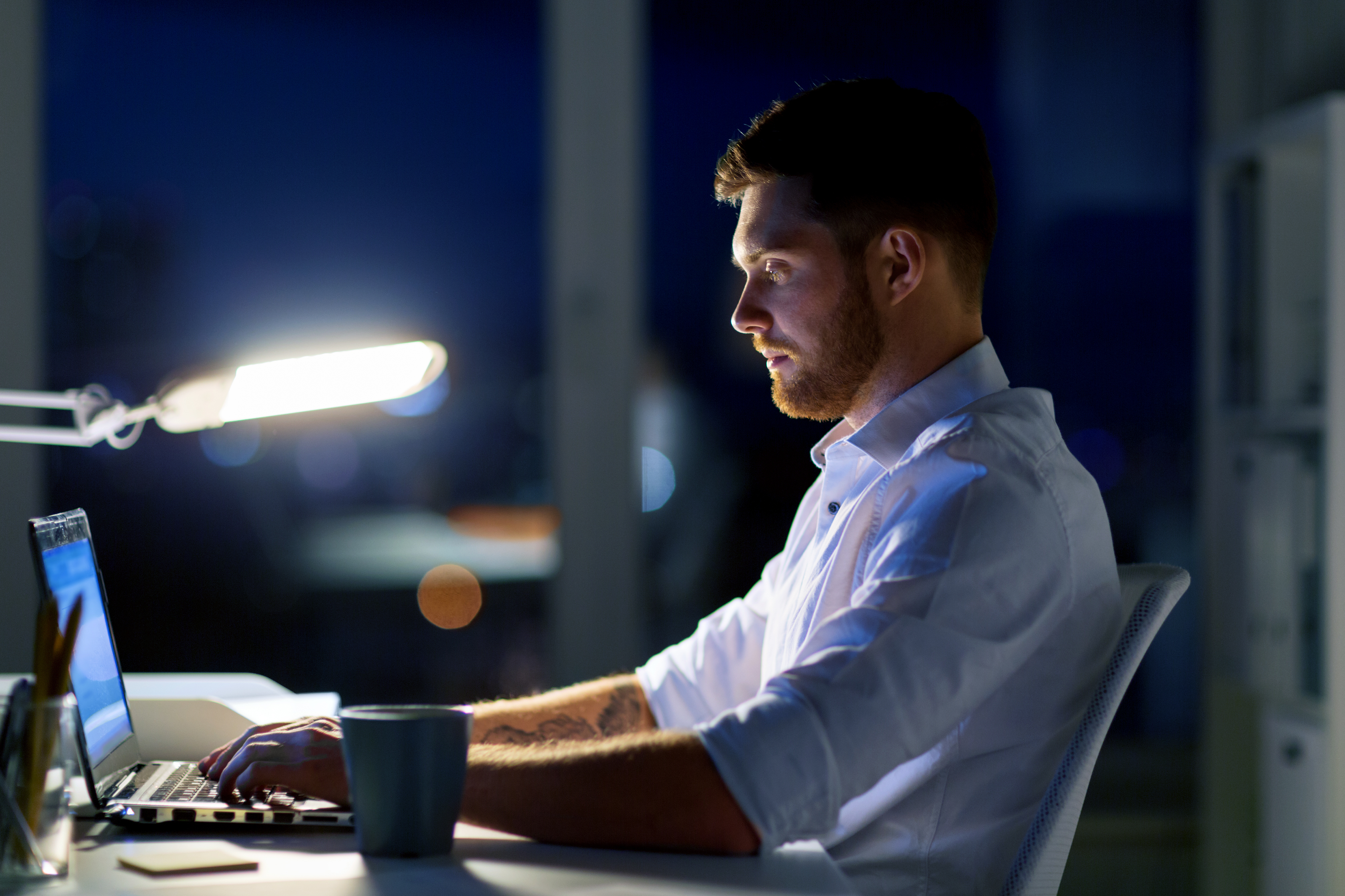 man-with-laptop-and-coffee-working-at-night-PCEBWBR